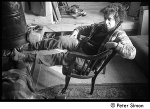 Thumbnail of Rico (Richard Wizansky) seated by a wood stove, Packer Corners commune