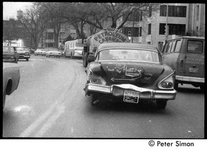 Thumbnail of Beat up old car driving down Cambridge street