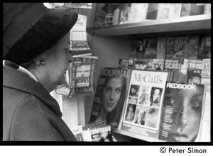 Thumbnail of Woman looking at magazines at a Cambridge newsstand