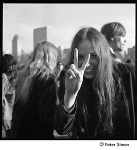 Thumbnail of Young woman flashing a peace sign at the Be-in, Central Park, New York City