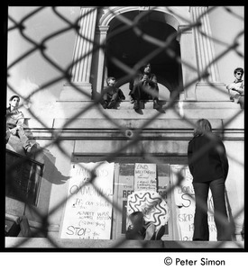Thumbnail of Civil War memorial on Cambridge Common seen through a chain link fence with             protesters and antiwar signs