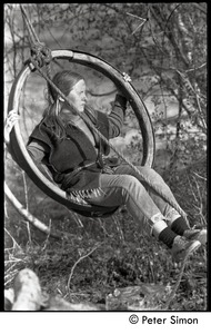 Thumbnail of Evan Mahaffy swinging from an old wheel hung in a tree, Packer Corners commune