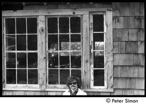 Thumbnail of Laurie Dodge standing outside a house window, Packer Corners commune