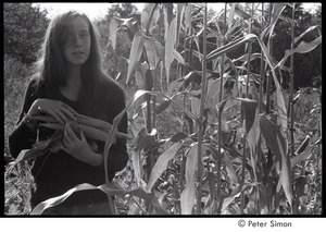 Thumbnail of Lacey Mason, holding corn and a tomato, Packer Corners commune