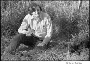 Thumbnail of Joe Pilati in tall grass, holding a book and looking at a puppy, Packer Corners commune