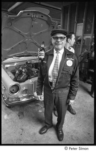 Thumbnail of Mechanic at Boston Volvo posing while coworker holds a beer over his shoulder