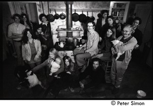 Thumbnail of Communards gathered around the wood stove, Montague Farm Commune kitchen Left side: James Tapley, Catherine Hutchison Rogers, Nina             Keller (seated), unidentified (seated), Peter Gould; Janis Frey holding baby Sequoya,             Nancy Wasserman (seated in front of stove); right side: John Wilton (seated by stove),             unidentified (seated on floor), Steve Marsden (rear), Harvey Wasserman, Steve Diamond             (arm on Wasserman's shoulder), Tony Mathews (seated), Alex Kelly (with cat)