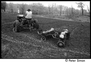 Thumbnail of Harvey Wasserman driving a tractor with disc tiller, Montague Farm Commune