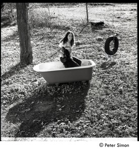 Thumbnail of Jenny Rose seated in a tub outdoors with dog and tire swing, Tree Frog Farm Commune