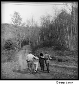 Thumbnail of Walking arm in arm down a dirt road, Tree Frog Farm Commune Laurie Dodge, Richard Wizansky, and unidentified (r. to l.)