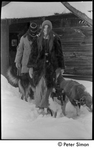 Thumbnail of Catherine Blinder in heavy winter coat, with masked communard [Elliot Blinder] and dogs, walking in             heavy snow, Tree Frog Farm commune