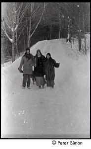Thumbnail of Elliot Blinder, Catherine Blinder, and unidentified woman (l. to r.) walking through heavy             snow, Tree Frog Farm commune