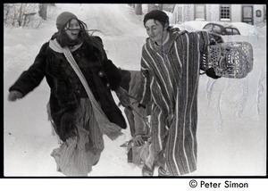 Thumbnail of Catherine Blinder and Fritz Hewitt walking through the heavy snow with snowshoes, Tree Frog Farm commune