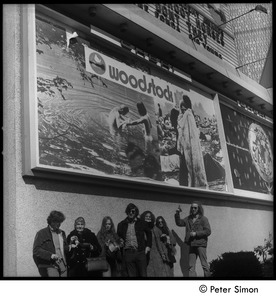 Thumbnail of Group beneath the Woodstock movie billboard, Cheri theater Includes Stephen Davis (far left), Lacey Mason (3rd from left), Tim Rossner             (center)