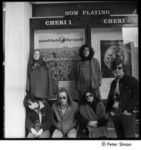Thumbnail of Group posed beneath the Woodstock movie poster, Cheri theater Includes Stephen Davis (seated far left), Lacey Mason (upper left), Tim             Rossner (far right)