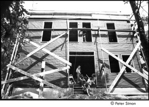 Thumbnail of James Taylor's house: group sitting in the doorway of Taylor's under construction house