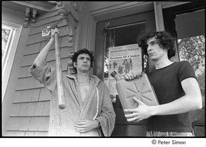 Thumbnail of David Doubilet holding a shovel and Stephen Davis holding a gasoline can, standing in front of the Boston Herald Traveler front page reporting the Kent State Shooting