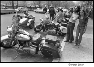 Thumbnail of Elliot Blinder holding a puppy and Lacey Mason standing by parked Boston Police motorcycles