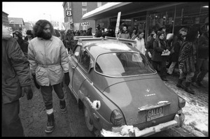 Thumbnail of Protesters in the streets of Montpelier, walking past a Saab automobile during a demonstration against the invasion of Laos