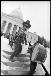 Thumbnail of Bread and Puppet Theater descending the steps at the Vermont State House, follow             a man with a bass drum, during a demonstration against the invasion of Laos