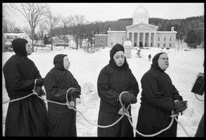 Thumbnail of Protesters from Bread and Puppet Theater, hands bound and dressed in cloaks and             masks, during a demonstration against the invasion of Laos at the Vermont State House
