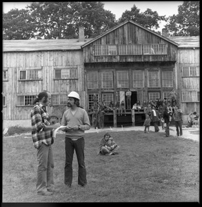 Thumbnail of Man in a hard hat talking with commune member outside the Brotherhood of the Spirit dormitory in Warwick, Mass.