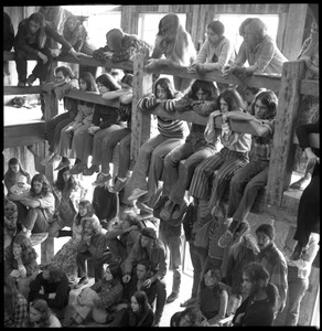 Thumbnail of Communal meeting inside the Brotherhood of the Spirit dormitory, Warwick, Mass. Commune members crowded on and under the second floor walkway