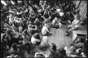 Thumbnail of Michael Metelica addressing a crowd of commune members at a meeting inside the Brotherhood             of the Spirit dormitory, Warwick, Mass. (view from above)