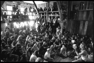 Thumbnail of Michael Metelica addressing a crowd of commune members at a meeting inside the Brotherhood             of the Spirit dormitory, Warwick, Mass. (view looking at audience over Michael's             shoulder)