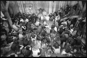Thumbnail of Michael Metelica addressing a crowd of commune members at a meeting inside the Brotherhood             of the Spirit dormitory, Warwick, Mass. (view from above, front)