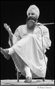 Thumbnail of Yogi Bhajan seated onstage, talking to the audience at the Kohoutek Celebration of Consciousness
