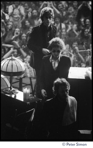 Thumbnail of Bob Dylan walking on stage at the Boston Garden, with Levon Helm in front and Robbie       Robertson behind