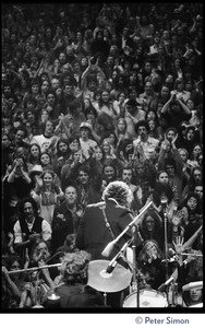 Thumbnail of Bob Dylan performing on stage at the Boston Garden with The Band, Levon Helm on       drums in the foreground View from rear stage looking over the performers and crowd, Dylan's back to the         camera