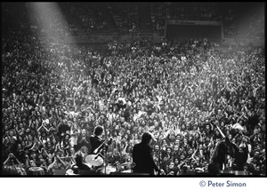 Thumbnail of Bob Dylan performing on stage at the Boston Garden with The Band View from rear stage looking over the performers and crowd