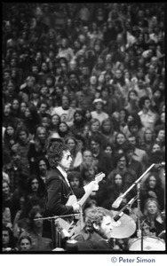 Thumbnail of Bob Dylan performing on stage at the Boston Garden with The Band, Levon Helm on       drums in the foreground View from rear stage looking over the performers and crowd