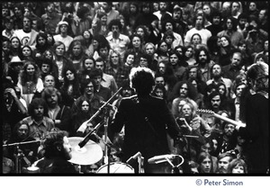 Thumbnail of Bob Dylan performing on stage at the Boston Garden with The Band View from rear stage looking over the performers silhouetted against the crowd