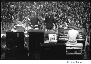 Thumbnail of Bob Dylan, Robbie Robertson, and Garth Hudson (from left) performing on stage at the Boston Garden with The Band View from rear stage looking over the performers silhouetted against the crowd