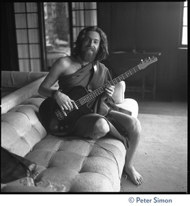 Thumbnail of Krishna Das, playing bass guitar, sitting on a couch in the Vicente Street house