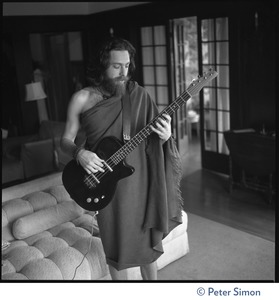 Thumbnail of Krishna Das, playing bass guitar in the Vicente Street house