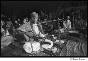 Thumbnail of Amazing Grace (band) performing at Winterland Ballroom, at a Ram Dass gathering Bhagavan Das (guitar), with Govind (violin) and Ram Dass in background