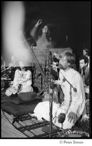 Thumbnail of Amazing Grace (band) performing at Winterland Ballroom, at a Ram Dass gathering Includes: Bhagavan Das (with dotara) and Cathy Brown (seated, at left)