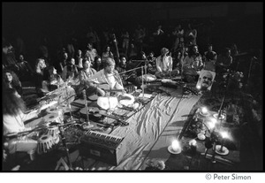 Thumbnail of Bhagavan Das playing guitar with the group Amazing Grace at the Ram Dass             gathering at the Winterland Ballroom In the background: group member Govind, Ram Dass, and Krishna Das, et al.,             along with portrait of Neem Karoli Baba