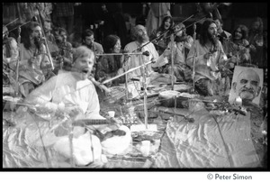 Thumbnail of Double exposure of the group Amazing Grace performing at the Ram Dass             gathering at the Winterland Ballroom Image includes Bhagavan Das (guitar), Ram Dass, and Krishna Das, among             others, and portrait of Neem Karoli Baba