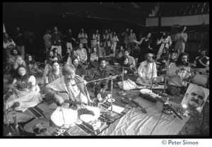 Thumbnail of Amazing Grace performing at the Ram Dass gathering at the Winterland Ballroom Image includes Bhagavan Das (guitar), Govind, Ram Dass, and Krishna Das, among             others, and portrait of Neem Karoli Baba