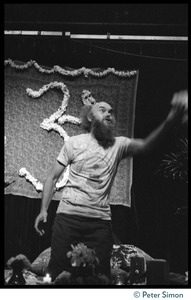 Thumbnail of Ram Dass gesturing energetically to the audience during his appearance at President       Theodore Roosevelt High School