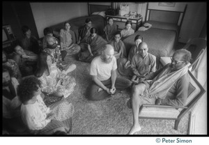 Thumbnail of Ram Dass, flower in hand, laughing, seated with others on the floor in front of Swami Muktananda