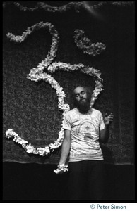 Thumbnail of Ram Dass on stage, eyes shut, during his appearance at President Theodore Roosevelt High School