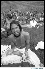 Thumbnail of Audience member seated on the lawn, clapping, as he awaits the appearance of Ram Dass at Andrews Amphitheater, University of       Hawaii