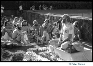 Thumbnail of Ram Dass seated on a small platform, arms raised, during his appearance at Andrews Amphitheater, University of       Hawaii