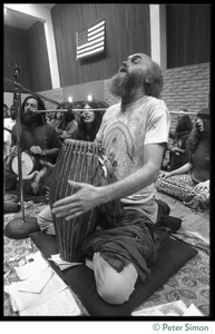 Thumbnail of Ram Dass seated on a floor with a drum during an appearance at the College of Marin, chanting Krishna Das in the background